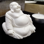 Seated miniature Buddha holding beads and sack